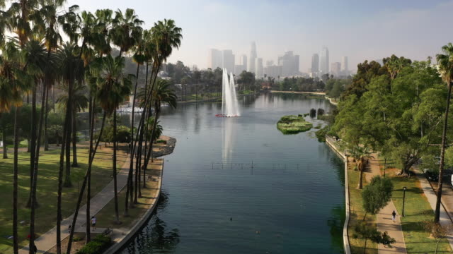 aerial: beautiful echo lake on a sunny day with view of the la skyline - los angeles, california - repetition stock videos & royalty-free footage