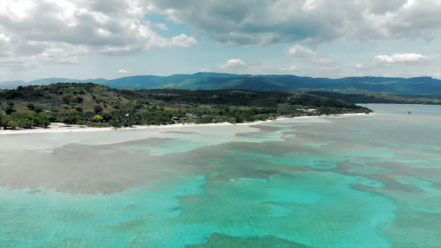 aerial: beautiful tropical bay with mountains in the distance - hispaniola stock videos & royalty-free footage