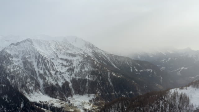 aerial: beautiful valley among snowy mountains with pine forests in south tyrol, italy - alto adige video stock e b–roll