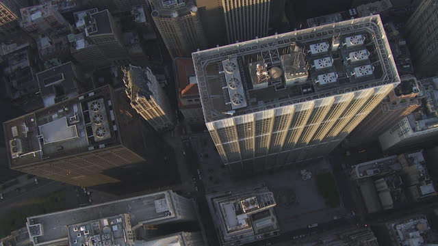 Aerial bird's eye pov of rooftops in downtown Manhattan city skyline. skyscrapers and high rise office or apartment buildings. multi-story. freeways or highways. city streets.