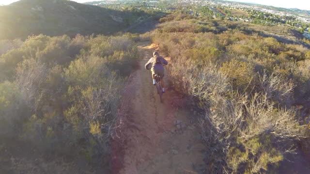 Aerial birds eye shot of young man mountain biking on a trail.