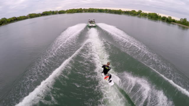aerial birds-eye drone view of a man wakeboarding behind a boat.  - slow motion - ウェイクボーディング点の映像素材/bロール