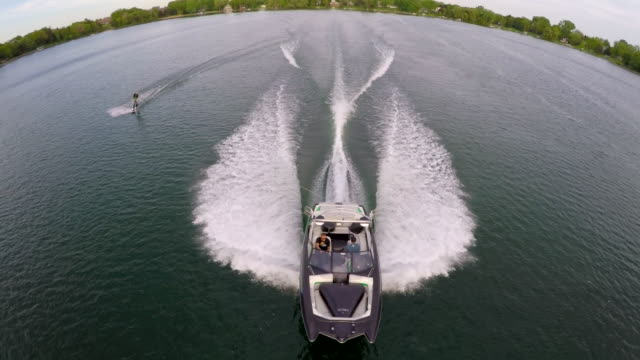 aerial birds-eye drone view of a man wakeboarding behind a boat. - wakeboarding stock videos and b-roll footage