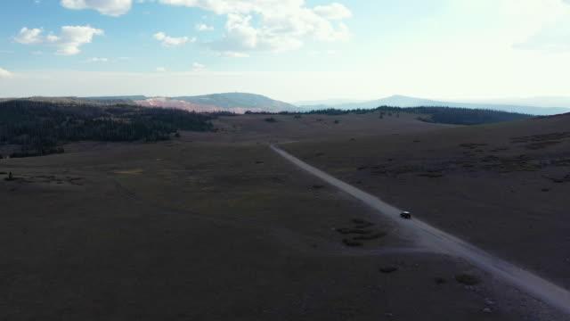 schwarzes suv aus der luft fährt durch utahs landschaft - land stock-videos und b-roll-filmmaterial