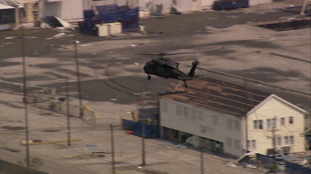 aerial blackhawk helicopter flying over industrial buildings and flooded neighborhood / new orleans, louisiana - 2005年点の映像素材/bロール