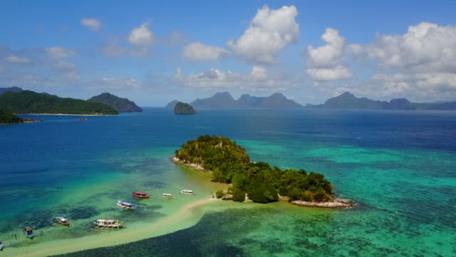 aerial: blue ocean, islands, sandbank and banca boats in palawan, philippines - anchored stock videos & royalty-free footage