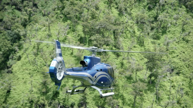 aerial blue/grey airbus h-130 helicopter flying l-r over river valley, kauai, hawaii; many views - helicopter stock videos & royalty-free footage