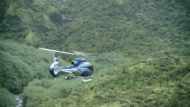 aerial blue/grey airbus h-130 helicopter flying l-r over valley, kauai, hawaii - kauai stock videos & royalty-free footage