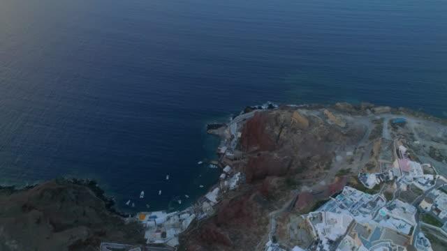 aerial: bluff along an ocean in santorini, greece - gebäudefries stock-videos und b-roll-filmmaterial