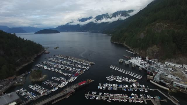 aerial: boat dock surrounded by tall, forest covered mountains - strength stock videos & royalty-free footage