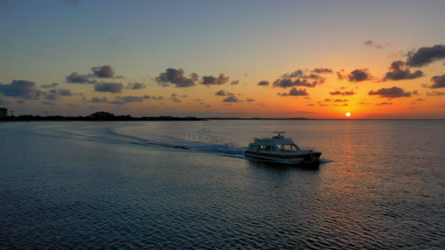 aerial: boat sailing past lovely orange sunset on the dark horizon - providenciales, turks and caicos - horizon stock videos & royalty-free footage