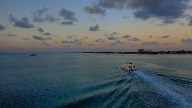 aerial: boat sailing through dark water after sunset near shore town - providenciales, turks and caicos - 帆点の映像素材/bロール