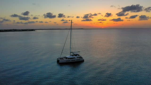 vídeos de stock e filmes b-roll de aerial: boat sitting peacefully in rippling water as the sun sets on the cloudy horizon - providenciales, turks and caicos - crepúsculo