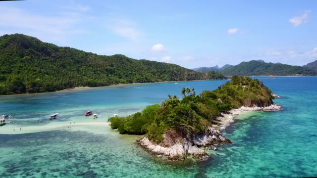 aerial: boats anchored between islands in blue ocean in palawan, philippines - anchored stock videos & royalty-free footage