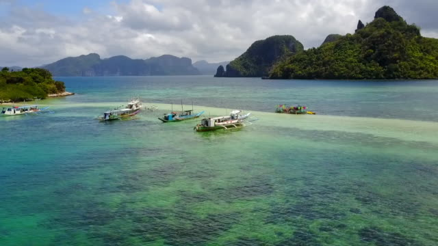 aerial: boats anchored in shallow ocean between islands in palawan, philippines - anchored stock videos & royalty-free footage