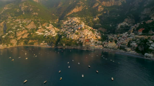 aerial: boats anchored in the calm ocean in front of a town on a cliff in positano, italy - anchored stock videos & royalty-free footage