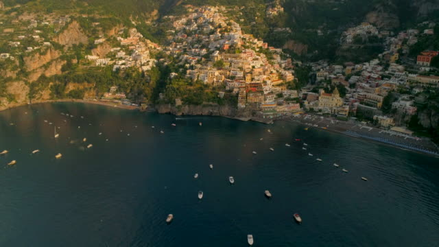 aerial: boats anchored in the ocean in front of a town on a cliff in positano, italy - anchored stock videos & royalty-free footage