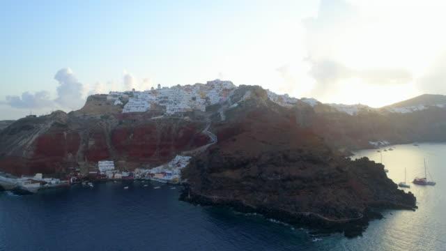 aerial: boats anchored in the ocean in santorini, greece - gebäudefries stock-videos und b-roll-filmmaterial