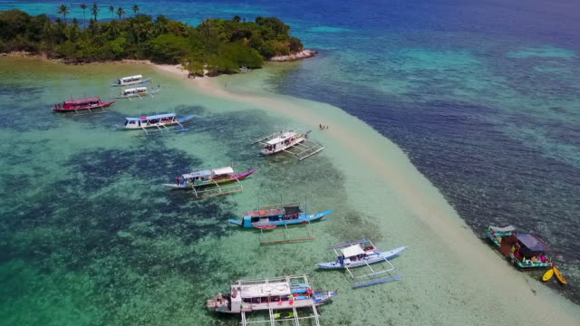 aerial: boats anchored near island and people on sandbank in palawan, philippines - anchored stock videos & royalty-free footage