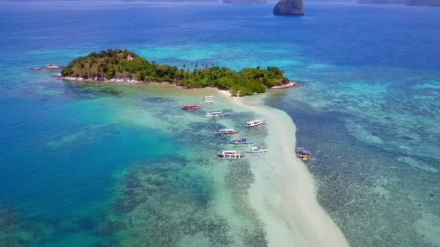 stockvideo's en b-roll-footage met aerial: boats anchored near island in blue ocean in palawan, philippines - voor anker gaan