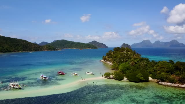 aerial: boats anchored near islands in blue ocean in palawan, philippines - anchored stock videos & royalty-free footage