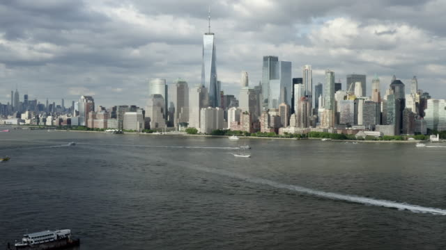 aerial: boats crossing the hudson river passing the freedom tower and other high rise buildings - new york city, new york - altri temi video stock e b–roll