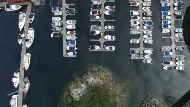 aerial: boats docked in water with reflection of clouds on water - pier stock videos & royalty-free footage