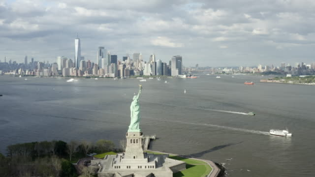 aerial: boats drive past the statue of liberty with new york city across the bay - new york city, new york - statue of liberty new york city stock videos & royalty-free footage