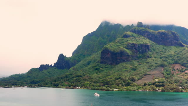 aerial: boats in an inlet of a tropical island with lush mountains, moorea, french polynesia - insel moorea stock-videos und b-roll-filmmaterial