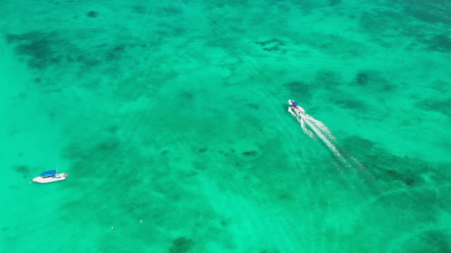 aerial: boats sitting and driving across a tropical ocean off the coast of tulum - tulum, mexico - tulum mexico stock videos & royalty-free footage