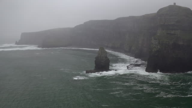 aerial: breezy waves crashing on rough cliff wall in misty winter in kerry, ireland - bay of water stock videos & royalty-free footage