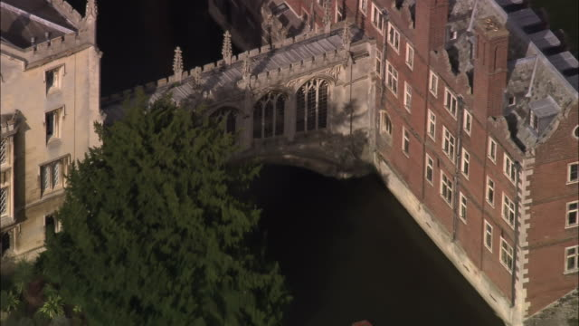 Aerial Bridge of Sighs over River Cam at Cambridge University / zoom out punt passing underneath