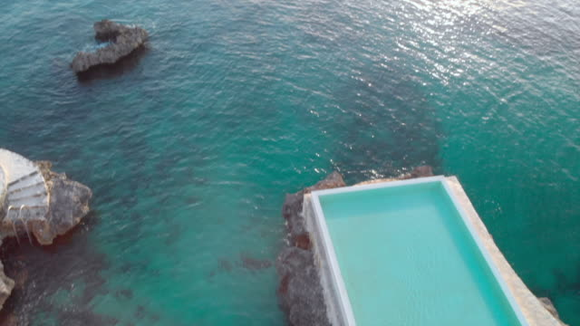 aerial: bright blue swimming pool next to the ocean at sunset - piscina pubblica all'aperto video stock e b–roll