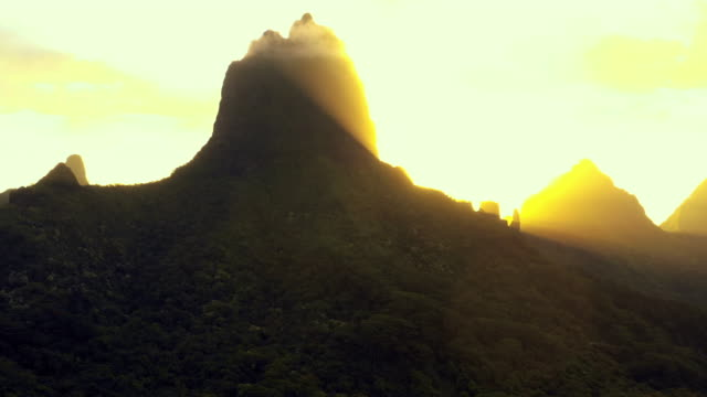 aerial: bright sun rays as it rises over moorea's mountains, moorea, french polynesia - insel moorea stock-videos und b-roll-filmmaterial