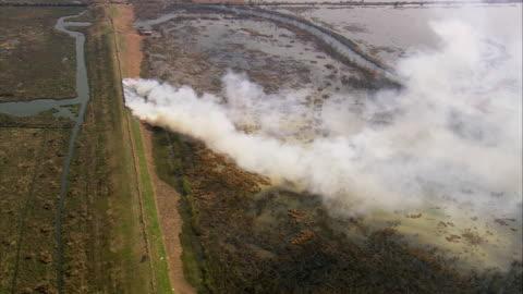 vidéos et rushes de aerial brush fire on train track / smoke billowing over marshy landscape / louisiana - 2005