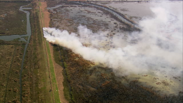 vídeos y material grabado en eventos de stock de aerial brush fire on train track / smoke billowing over marshy landscape / louisiana - 2005