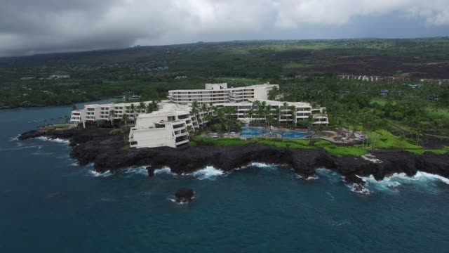 aerial: buildings on grassy, tree filled, rocky ocean shore - big island hawaii islands stock videos & royalty-free footage