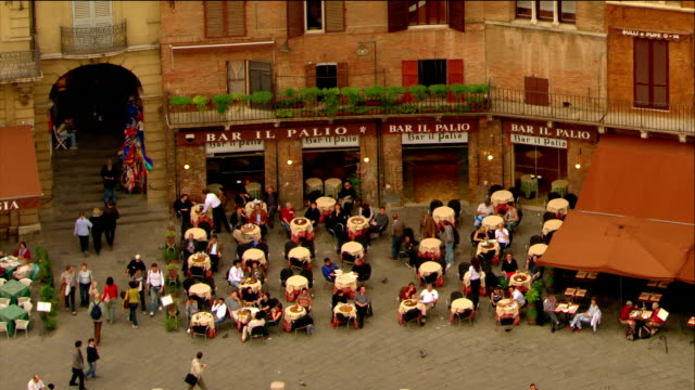 aerial cafe in piazza del campo / close up torre del mangia / pull out to palazzo pubblico / siena, italy - palazzo pubblico stock videos and b-roll footage