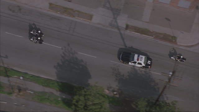 stockvideo's en b-roll-footage met aerial. camera flying above police motorcade. three black suburbans in the middle surrounded by police motorcycles and cars. shot in slow motion - omgeven