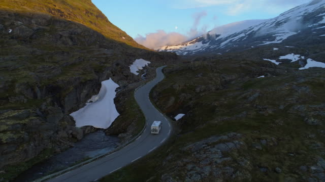 aerial: camper van moving on winding road against mountain range during winter - dalsnibba mountain plateau, norway - camper van stock videos & royalty-free footage