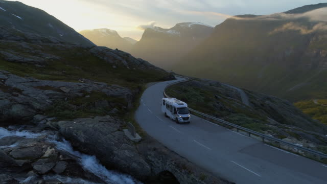 aerial: camper van on winding road against mountain range during winter - dalsnibba mountain plateau, norway - furgone video stock e b–roll