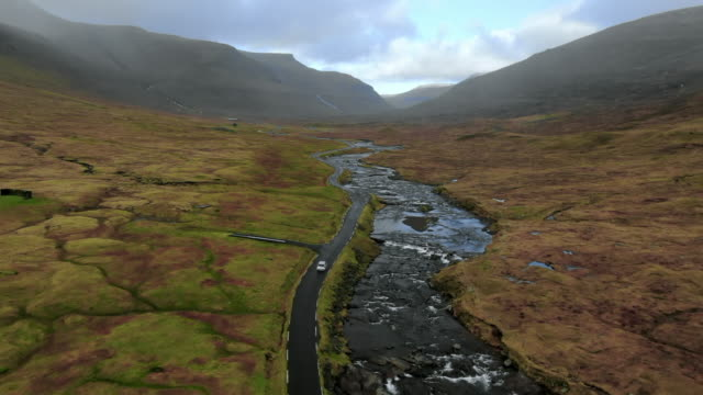 vídeos y material grabado en eventos de stock de aerial car drives windy road by stream through beautiful green valley, car stops, streymoy island, faroe islands - lago
