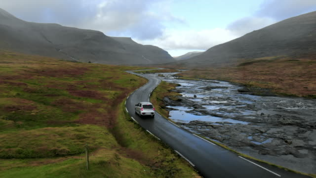 stockvideo's en b-roll-footage met aerial car stopped on winding road in beautiful valley by stream, aerial drone moves back and ascends, streymoy island, faroe islands - rug