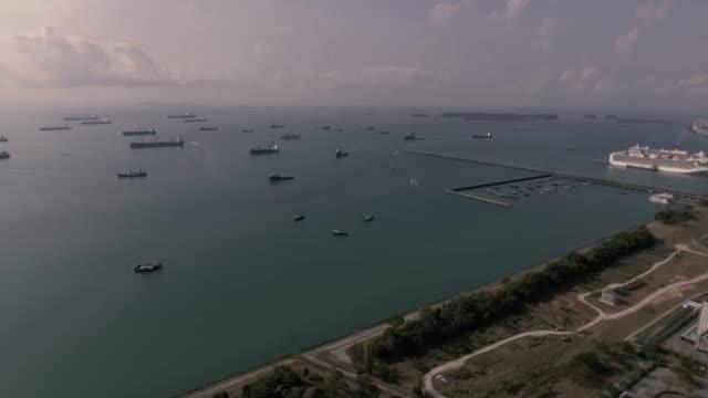 stockvideo's en b-roll-footage met luchtvracht schepen verankerd in de zee in singapore - anchored