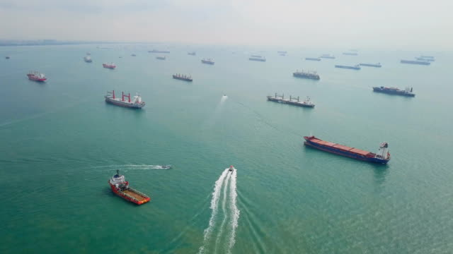 stockvideo's en b-roll-footage met luchtfoto vrachtschepen verankerd in de zee. singapore - haven
