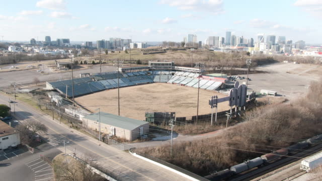 aerial: cars and a slow train move past an old abandoned minor league stadium with a view of distant nashville skyline - dugout stock videos & royalty-free footage