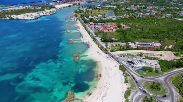 aerial: cars driving along waterfront road near beach and neighborhood - nassau, bahamas - bahamas stock videos & royalty-free footage