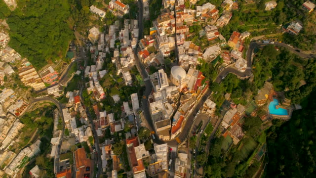 aerial: cars driving on a road that bends around a town on a cliff in positano, italy - liguria stock videos & royalty-free footage