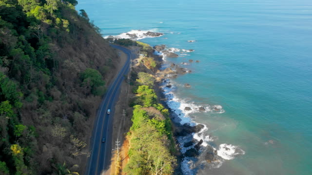 aerial: cars driving on cliff road at the base of a mountain near bright blue water - jaco, costa rica - costa rica stock videos & royalty-free footage
