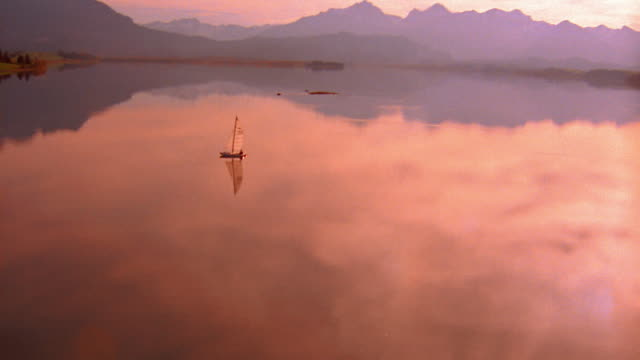 Aerial catamaran with sails on mountain lake / mountains in background and reflected on water / Germany